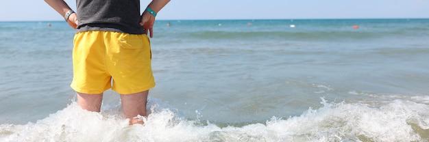 Hombre en pantalones cortos amarillos está hasta las rodillas en el mar