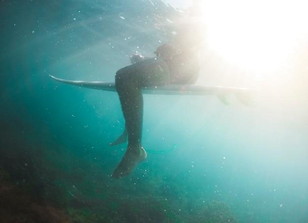 Hombre en pantalones cortos sentado en la tabla de surf bajo el agua