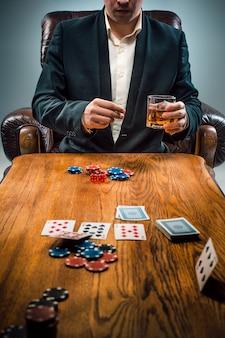El hombre, papas fritas para jugar, beber y jugar a las cartas.