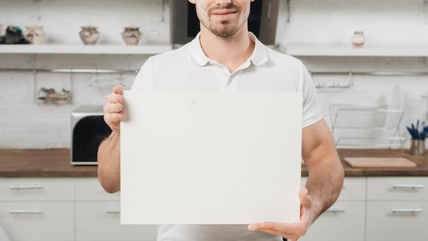 Hombre con papel en blanco en cocina