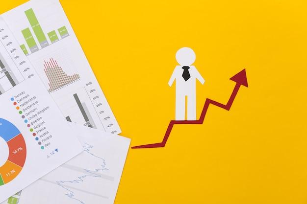 Hombre de papel con flecha de crecimiento, gráficos y tablas. símbolo de éxito económico y social, escalera al progreso.