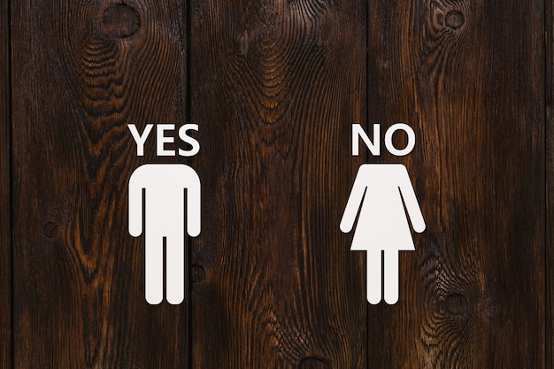 Hombre de papel con texto sí y mujer con no sobre fondo de madera. concepto de divorcio o amor no correspondido. imagen conceptual abstracta