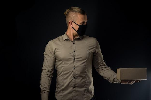 Hombre con paquete sobre pared negra