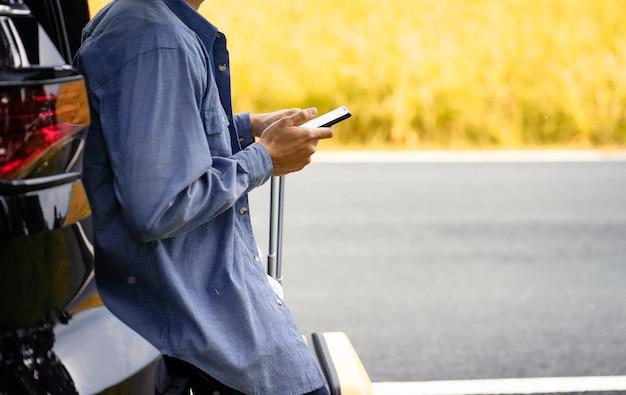Hombre parado en el auto con su teléfono móvil y equipaje