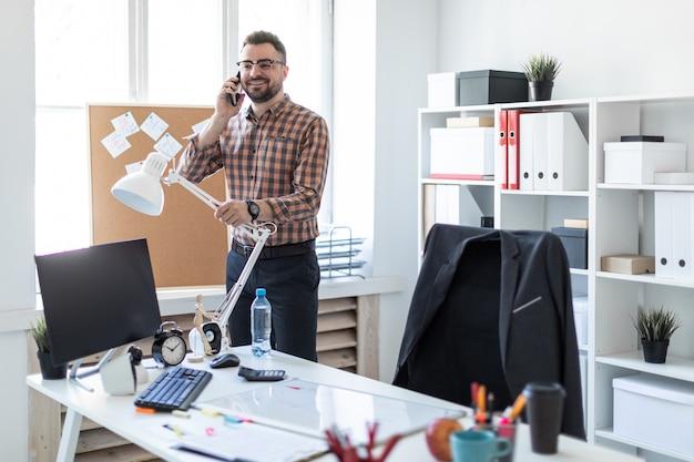 Un hombre está parado en la oficina cerca de la ventana y hablando por teléfono.