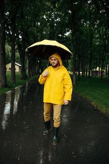 Hombre con paraguas caminando en el parque de verano en día lluvioso. persona del sexo masculino en capa de lluvia y botas de goma, clima húmedo en el callejón