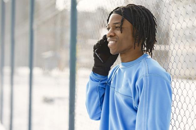 Hombre en un parque de invierno. chico africano entrenando afuera.