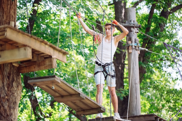 El hombre pasa su tiempo libre en un curso de cuerdas. hombre comprometido en el parque de cuerdas.