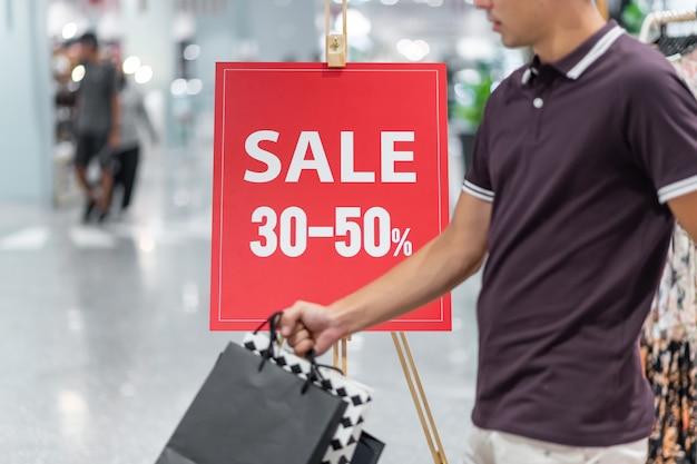 Hombre pasando cartel con mensaje de venta