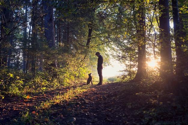Hombre paseando a su perro en el bosque