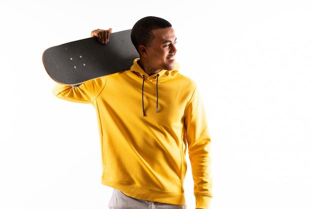 Hombre patinador afroamericano sobre pared blanca aislada