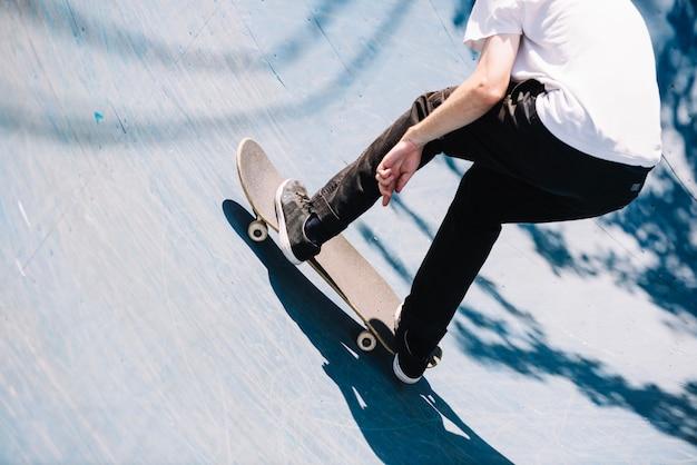 Hombre patinador de cultivos en la rampa