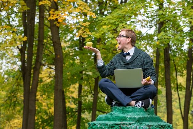 Un hombre en un pedestal que pretende ser una estatua con una computadora portátil en la mano con la expresión a medida que surgió la brillante idea