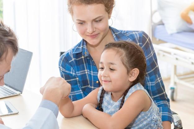 Hombre pediatra que da el golpe de puño (high five to), tranquilizador y hablando del niño en la cirugía.