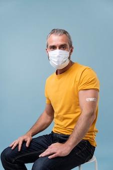 Hombre con pegatina en el brazo después de recibir una vacuna