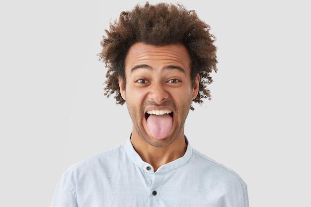 Hombre con peinado afro muestra la lengua mientras nota algo repugnante, hace muecas, demuestra un carácter obstinado