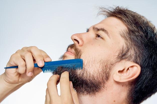 Un hombre con un peine en sus manos cuidando su barba.