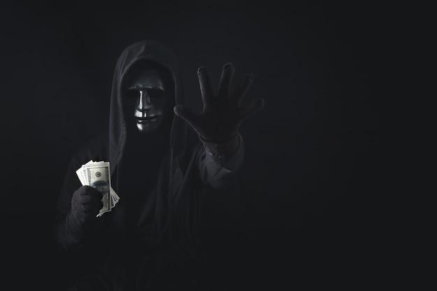 Hombre peligroso hacker anónimo encapuchado mostrando gesto de parada y sosteniendo el billete.