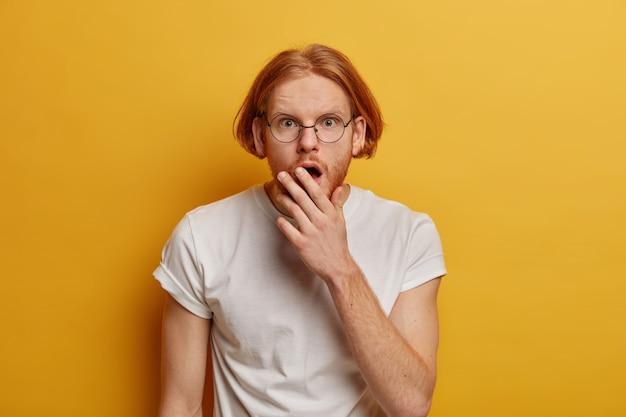Hombre pelirrojo aturdido reacciona sobre los descuentos de temporada, mira con estupor, se tapa la boca, usa gafas y camiseta blanca, aislado en la pared amarilla, se olvidó de algo. omg expresión