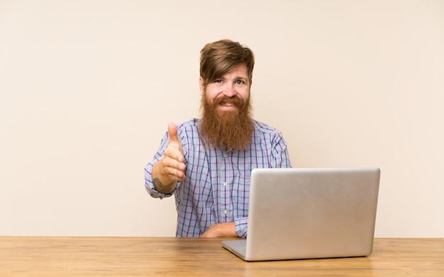 Hombre pelirrojo con barba larga en una mesa con un apretón de manos portátil después de un buen trato