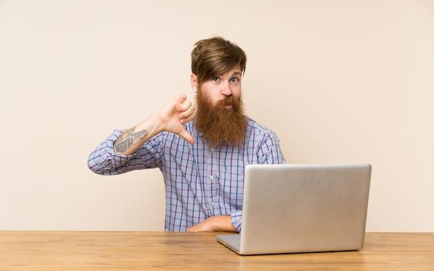 Hombre pelirrojo con barba larga en una mesa con una computadora portátil que muestra el pulgar hacia abajo