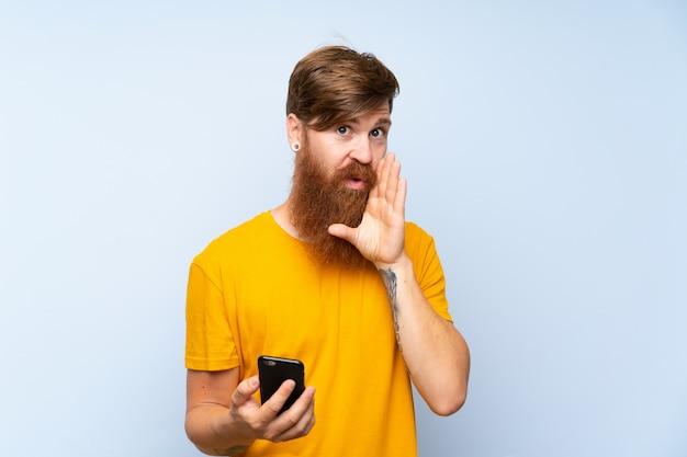Hombre pelirrojo con barba larga con un móvil sobre pared azul aislada susurrando algo