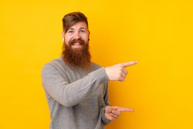 Hombre pelirrojo con barba larga sobre pared amarilla aislada apuntando el dedo hacia un lado y presentando un producto