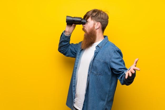 Hombre pelirrojo con barba larga sobre pared amarilla aislada con binoculares negros