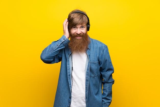 Hombre pelirrojo con barba larga sobre pared amarilla aislada escuchando música con auriculares