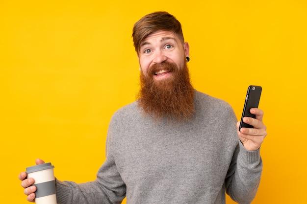 Hombre pelirrojo con barba larga sobre pared amarilla aislada manteniendo una conversación con el teléfono móvil con alguien