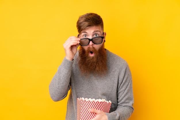Hombre pelirrojo con barba larga sobre pared amarilla aislada sorprendido con gafas 3d y sosteniendo un gran cubo de palomitas de maíz