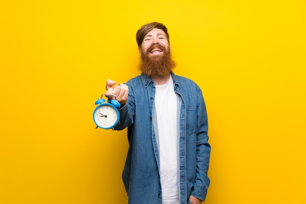 Hombre pelirrojo con barba larga sobre pared amarilla aislada con vintage despertador