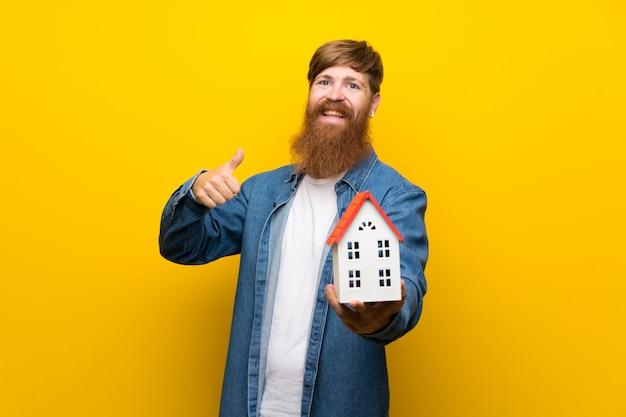 Hombre pelirrojo con barba larga sobre pared amarilla sosteniendo una casita