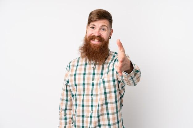 Hombre pelirrojo con barba larga sobre pared blanca aislada estrechándole la mano para cerrar un buen trato