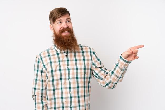 Hombre pelirrojo con barba larga sobre la pared blanca aislada que señala el dedo hacia un lado