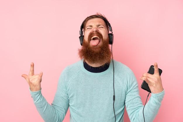 Hombre pelirrojo con barba larga sobre pared rosa aislado