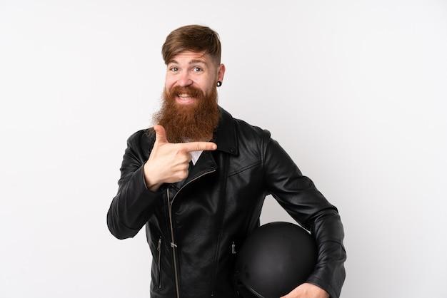 Hombre pelirrojo con barba larga sosteniendo un casco de motocicleta sobre pared blanca aislada apuntando con el dedo hacia un lado