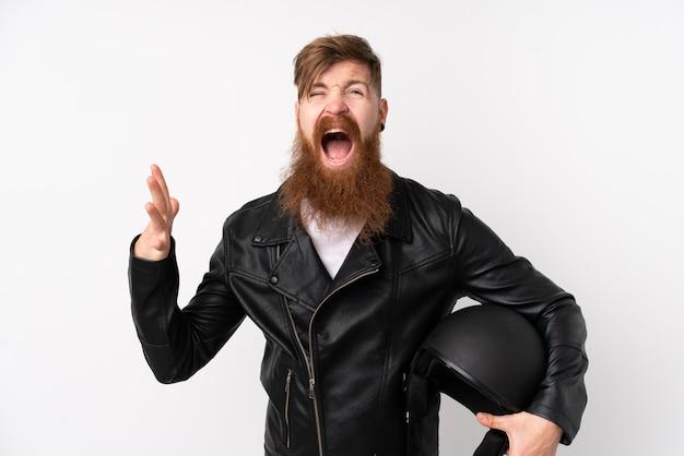 Hombre pelirrojo con barba larga sosteniendo un casco de motocicleta sobre pared blanca aislada infeliz y frustrado con algo