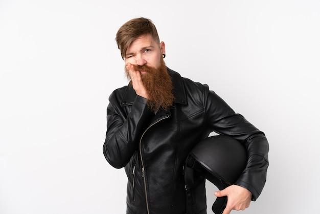 Hombre pelirrojo con barba larga sosteniendo un casco de motocicleta sobre pared blanca aislada infeliz y frustrado