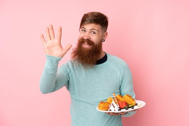 Hombre pelirrojo con barba larga sosteniendo gofres sobre pared rosa aislado saludando con la mano con expresión feliz
