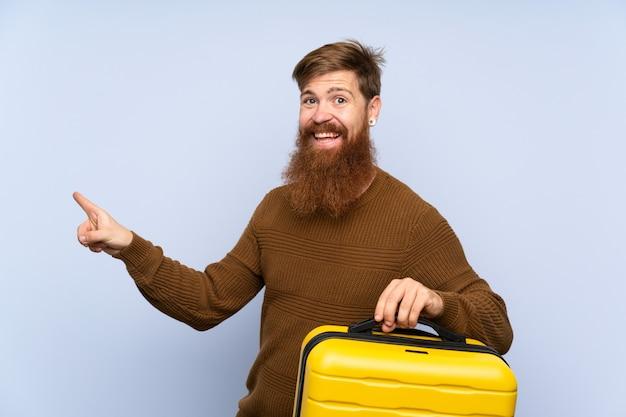 Hombre pelirrojo con barba larga sosteniendo una maleta sorprendido y apuntando con el dedo a un lado