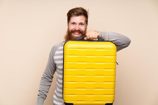 Hombre pelirrojo con barba larga sosteniendo un maletín vintage