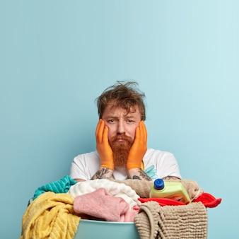 Hombre pelirrojo desesperado insatisfecho con cabello desordenado, toca las mejillas con ambas manos, con exceso de trabajo, tiene un montón de toallas sucias, se para sobre una pared azul, espacio en blanco para su contenido publicitario