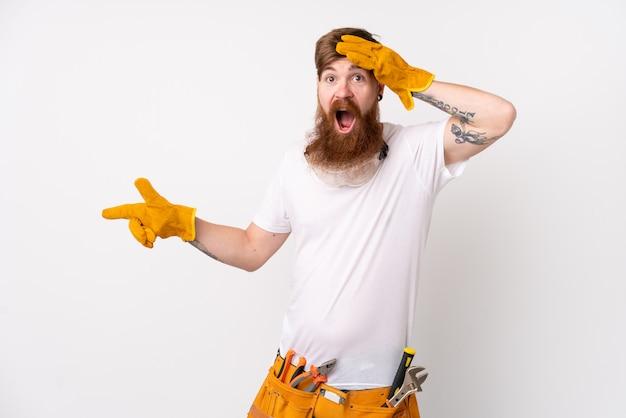 Hombre pelirrojo electricista con barba larga sobre pared blanca aislada sorprendido y apuntando con el dedo al lado