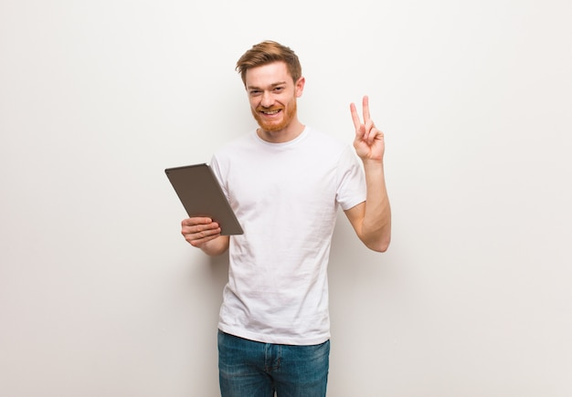 Hombre pelirrojo joven que muestra el número dos. sosteniendo una tableta.