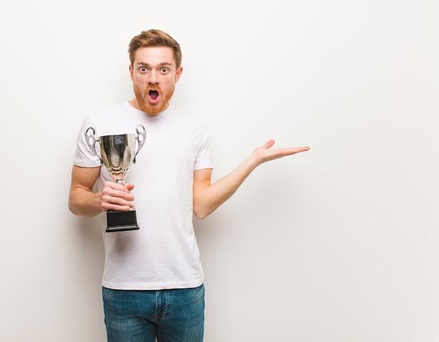 Hombre pelirrojo joven sosteniendo algo en la mano de la palma. sosteniendo un trofeo.