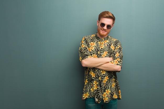 Hombre pelirrojo joven vistiendo ropa exótica de verano cruzando los brazos, sonriente y relajado