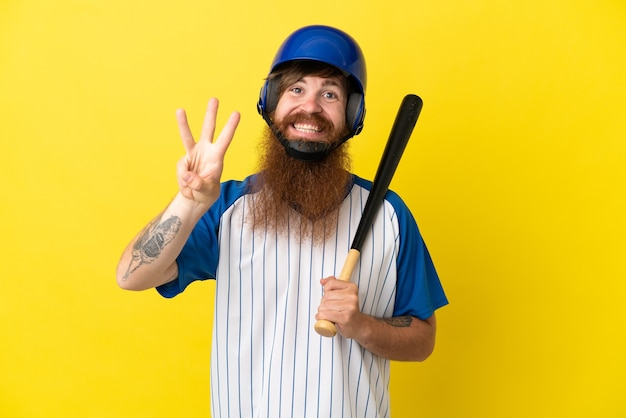 Hombre pelirrojo jugador de béisbol con casco y bate aislado sobre fondo amarillo feliz y contando tres con los dedos