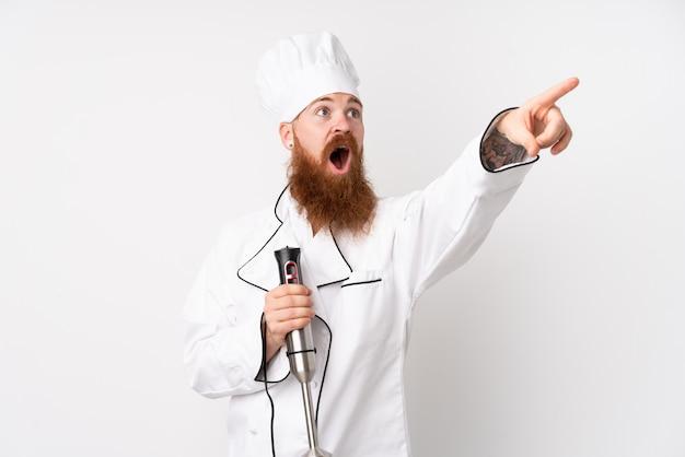 Hombre pelirrojo que usa la batidora de mano sobre la pared blanca aislada apuntando lejos