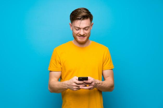Hombre pelirrojo sobre pared azul enviando un mensaje con el móvil